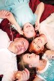 Glückliche Familie, die mit Weihnachtslichtgirlande nahe dem Weihnachtsbaum lächelt Überarbeiteter Schuss der Draufsicht lizenzfreie stockfotografie