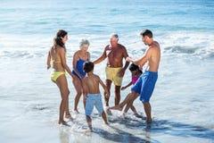 Glückliche Familie, die mit Wellen spielt Stockbild