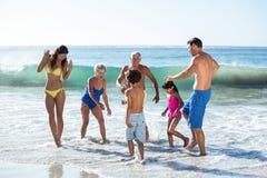 Glückliche Familie, die mit Wellen spielt Stockfotografie