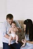 Glückliche Familie, die Mutter und Vati ` s aus Baby besteht Glückliche Familien-Verhältnisse Stockfoto