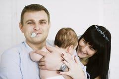 Glückliche Familie, die Mutter und Vati ` s aus Baby besteht Glückliche Familien-Verhältnisse Stockfotos