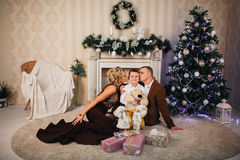 Glückliche Familie, die nahe Weihnachtsbaum sitzt Stockfotografie