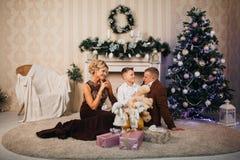 Glückliche Familie, die nahe Weihnachtsbaum sitzt Lizenzfreies Stockfoto
