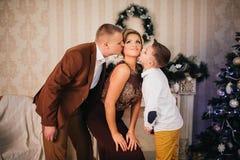 Glückliche Familie, die nahe Weihnachtsbaum sitzt Stockfotos