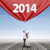 Glückliche Familie, die neue Zukunft im Jahre 2014 ergreift Lizenzfreies Stockfoto
