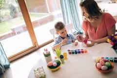 Glückliche Familie, die Ostereier malt stockfotografie