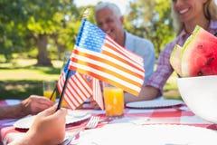 Glückliche Familie, die Picknick hat und amerikanische Flagge hält Stockfoto