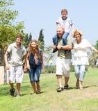 Glückliche Familie, die in Richtung zur Kamera läuft Stockfotos