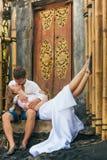 Glückliche Familie, die romantischen Flitterwochenfeiertag auf schwarzem Sandstrand genießt Stockbild