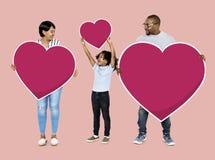 Glückliche Familie, die rote Herzikonen hält lizenzfreies stockbild