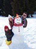 Glückliche Familie, die Schneemann bildet Stockbild