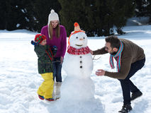 Glückliche Familie, die Schneemann bildet Lizenzfreie Stockbilder