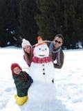 Glückliche Familie, die Schneemann bildet Lizenzfreies Stockfoto