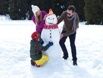 Glückliche Familie, die Schneemann bildet Stockfotografie