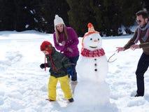 Glückliche Familie, die Schneemann bildet Stockfoto