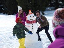Glückliche Familie, die Schneemann bildet Stockfotos
