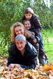 Glückliche Familie, die sich draußen im Herbst entspannt Stockbild