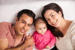 Glückliche Familie, die sich zu Hause in einem Bett entspannt Stockfotos