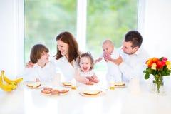 Glückliche Familie, die am Sonntag Morgen frühstückt Stockbild