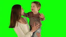 Glückliche Familie, die Spaß auf einem grünen Schirm hat stock footage