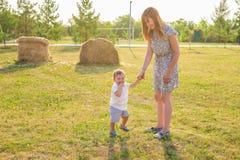 Glückliche Familie, die Spaß hat Baby und seine Mutter, die draußen spielen stockfoto