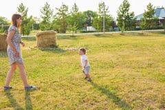 Glückliche Familie, die Spaß hat Baby und seine Mutter, die draußen spielen lizenzfreies stockfoto