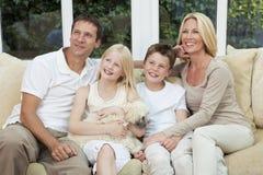 Glückliche Familie, die Spaß hat, mit Haustier-Hund zu sitzen Lizenzfreie Stockbilder