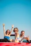 Glückliche Familie, die Spaß im roten Cabriolet hat stockfotografie