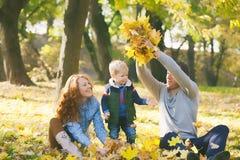 Glückliche Familie, die Spaß im städtischen Park des Herbstes hat Stockfotos