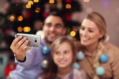 Glückliche Familie, die Spaß während der Weihnachtszeit hat und selfie nimmt Lizenzfreies Stockfoto