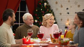 Glückliche Familie, die traditionelles Weihnachts, wenig Mädchen erzählt lustige Geschichten zu Abend isst stock video