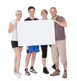 Glückliche Familie, die unbelegtes Schild anhält Lizenzfreie Stockbilder