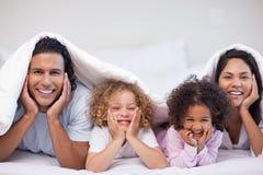 Glückliche Familie, die unter der Decke sich versteckt Lizenzfreie Stockfotos