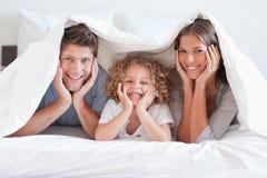 Glückliche Familie, die unter einem Duvet aufwirft stockfotografie
