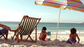 Glückliche Familie, die unter Sonnenschirm stillsteht stock footage