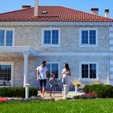 Glückliche Familie, die vor neuem modernem Haus aufwirft stockfoto