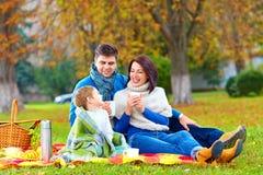 Glückliche Familie, die warmen Tee auf Herbstpicknick trinkt Stockfotos