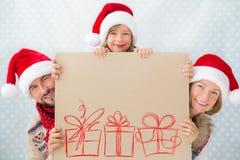 Glückliche Familie, die Weihnachtskarte hält Stockfoto
