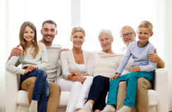 Glückliche Familie, die zu Hause auf Couch sitzt Stockfoto