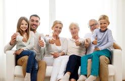 Glückliche Familie, die zu Hause auf Couch sitzt Stockbilder