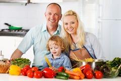 Glückliche Familie, die zu Hause ein gesundes Abendessen vorbereitet. Lizenzfreie Stockfotos