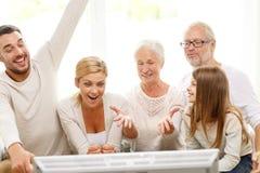 Glückliche Familie, die zu Hause fernsieht Stockbild