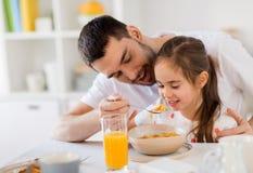 Glückliche Familie, die zu Hause Flocken zum Frühstück isst stockfotografie