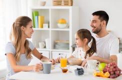 Glückliche Familie, die zu Hause frühstückt Stockbild