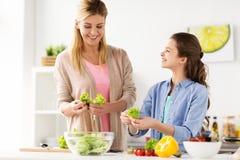Glückliche Familie, die zu Hause Küche des Salats kocht Lizenzfreie Stockfotografie