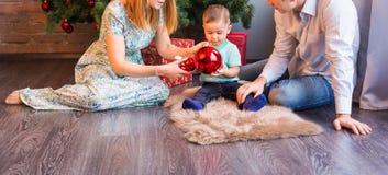 Glückliche Familie, die zu Hause mit Weihnachtsbällen spielt stockfotografie