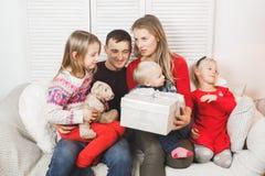 Glückliche Familie, die zu Hause Weihnachtsgeschenke hält stockfotografie