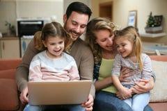 Glückliche Familie, die zu Hause Zeit verbringt und auf dem Laptop schaut Fa stockfotografie
