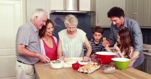 Glückliche Familie, die zusammen Biskuite kocht stock footage