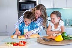 Glückliche Familie, die zusammen das Mittagessen vorbereitet stockfotos